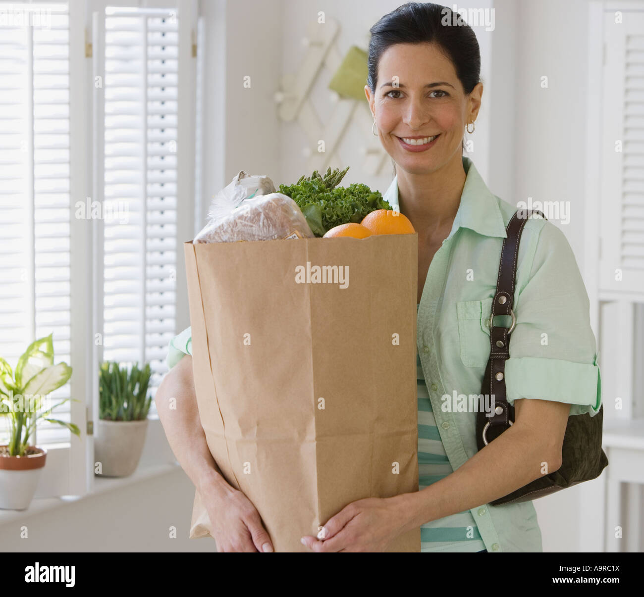 Woman holding bag of groceries in kitchen Photo Stock