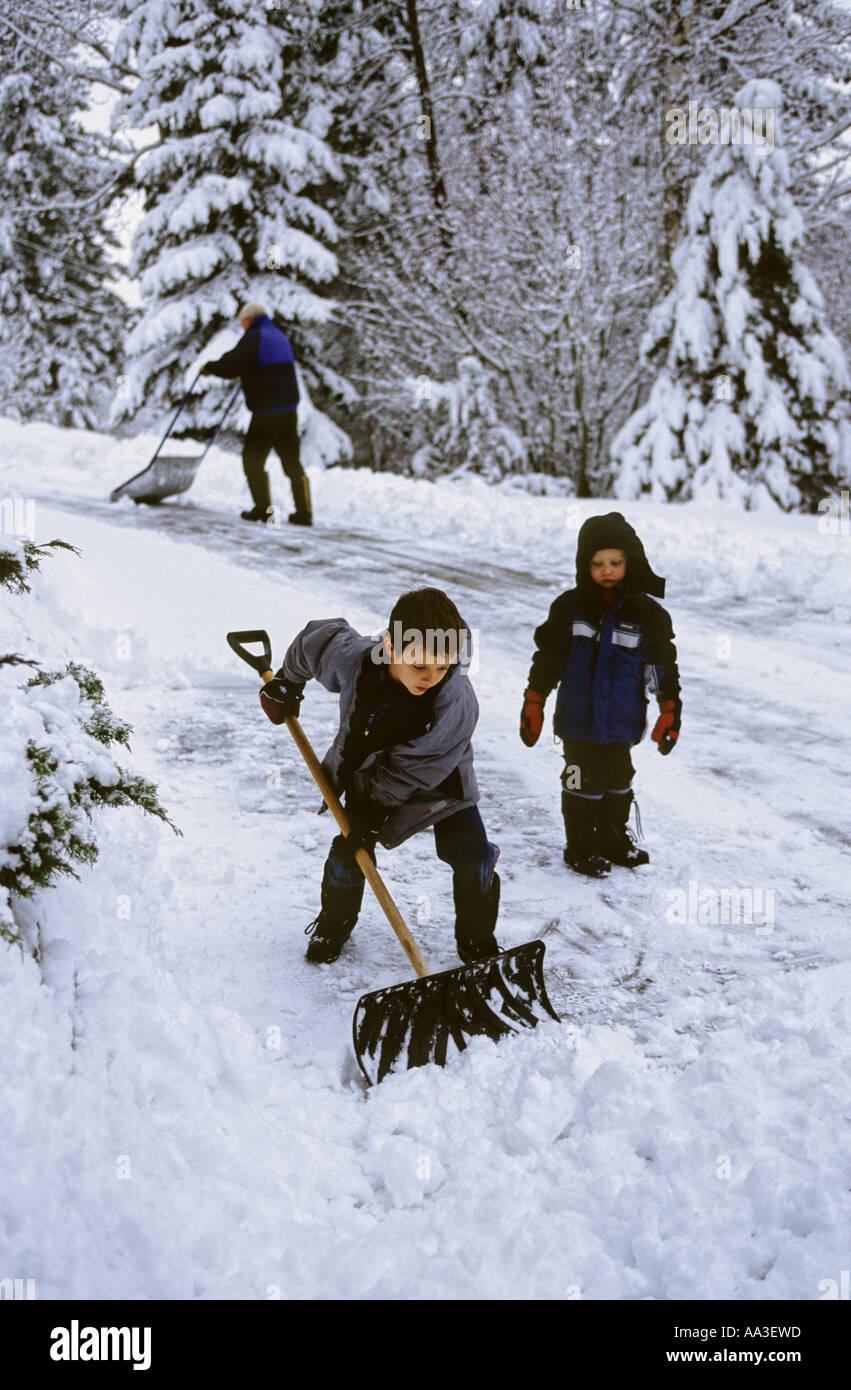 Grand-père et les petits-enfants de pelleter de la neige de l'allée de Salmon Arm, BC Canada Photo Stock