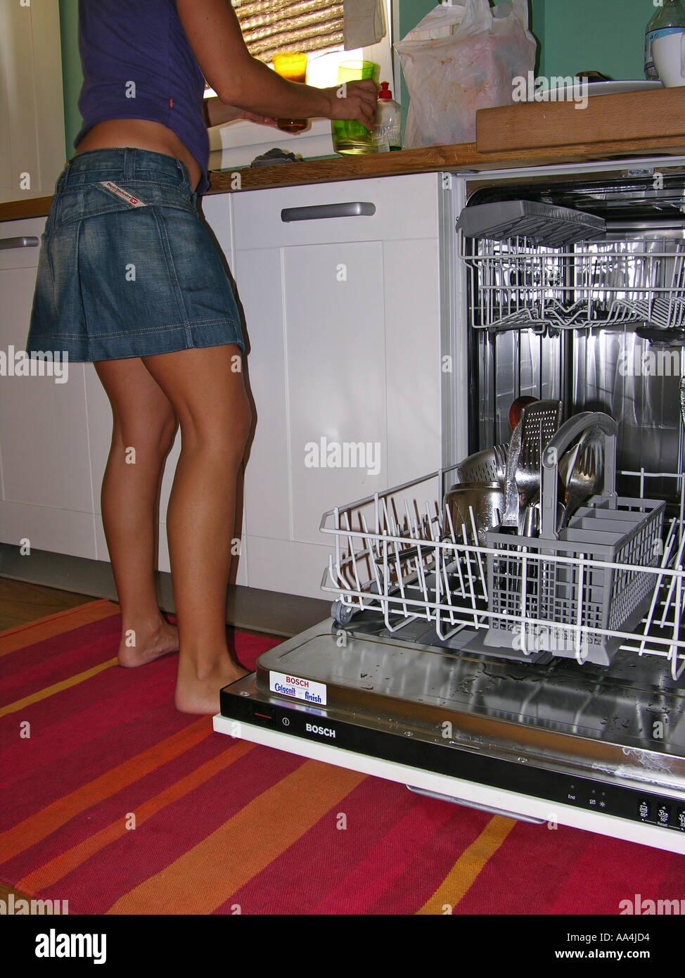 Vue arrière du côté d'une femme le chargement d'un lave-vaisselle Photo Stock