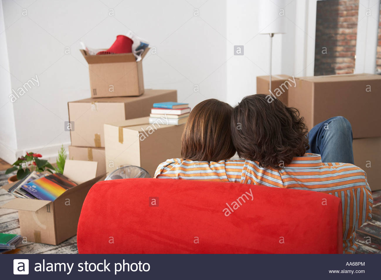 Vue arrière du couple sur red chair in house with cardboard boxes Photo Stock