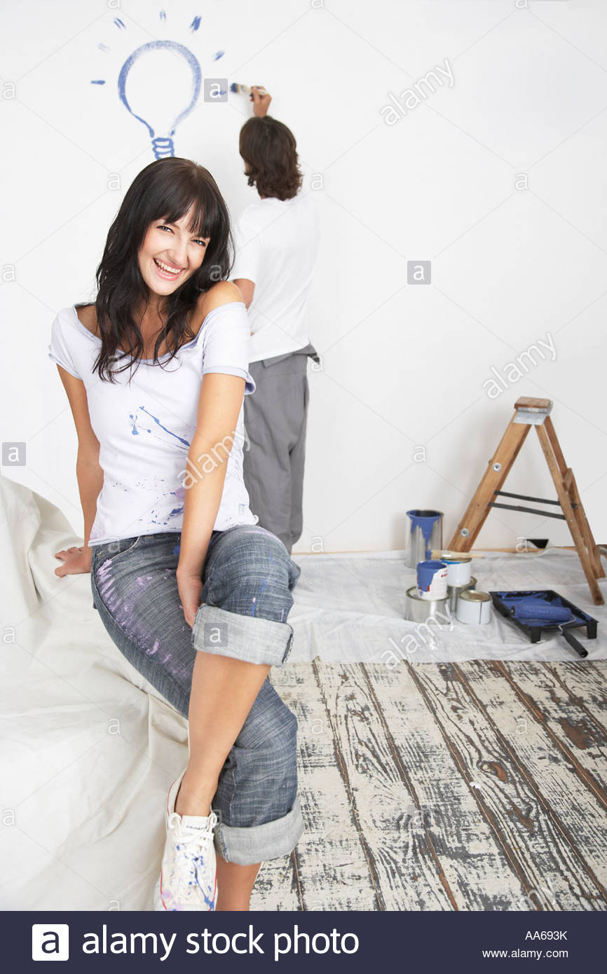 Man Painting Light bulb sur mur et woman on sofa Photo Stock