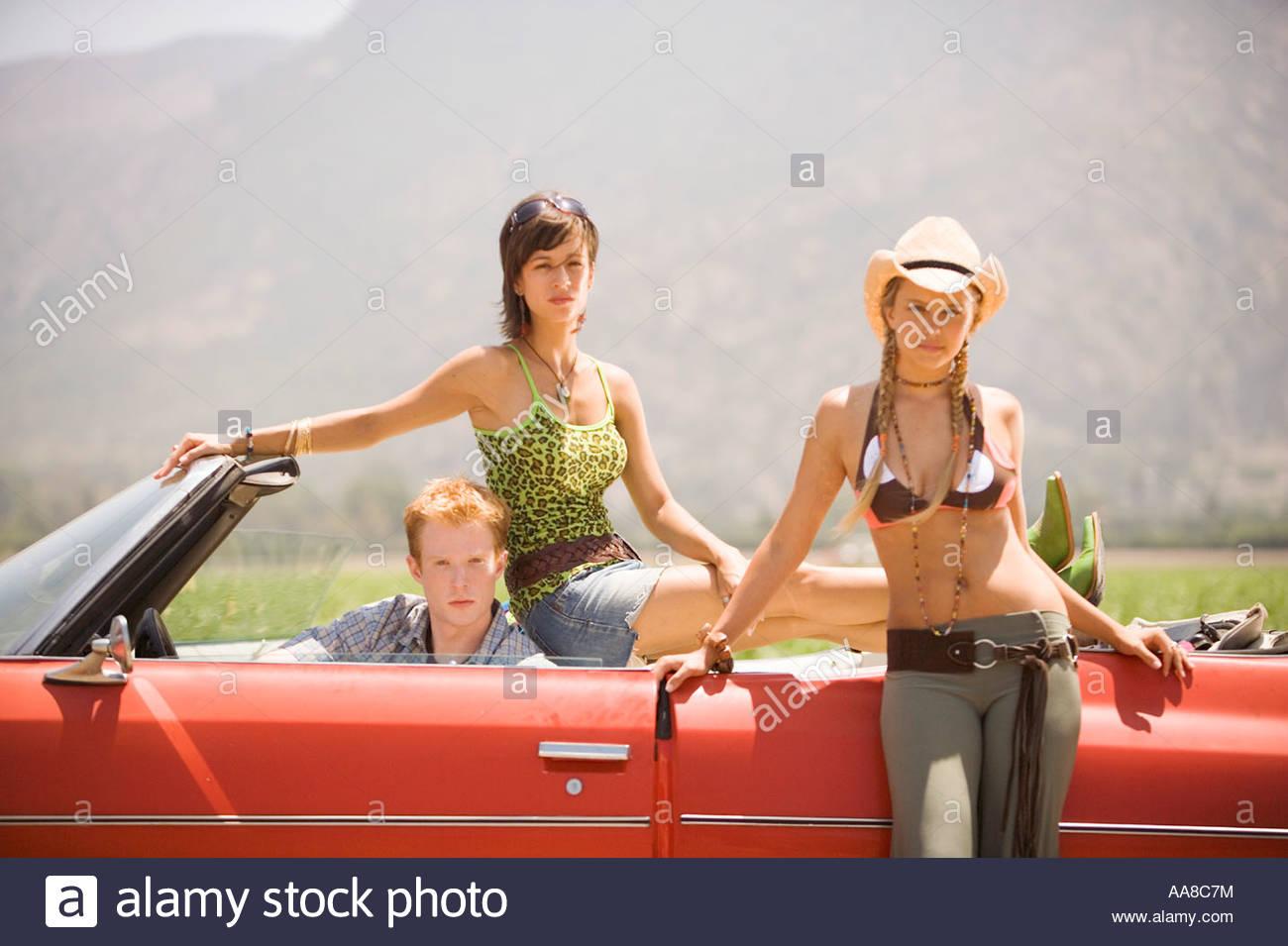 Les jeunes posant autour d'une voiture Photo Stock