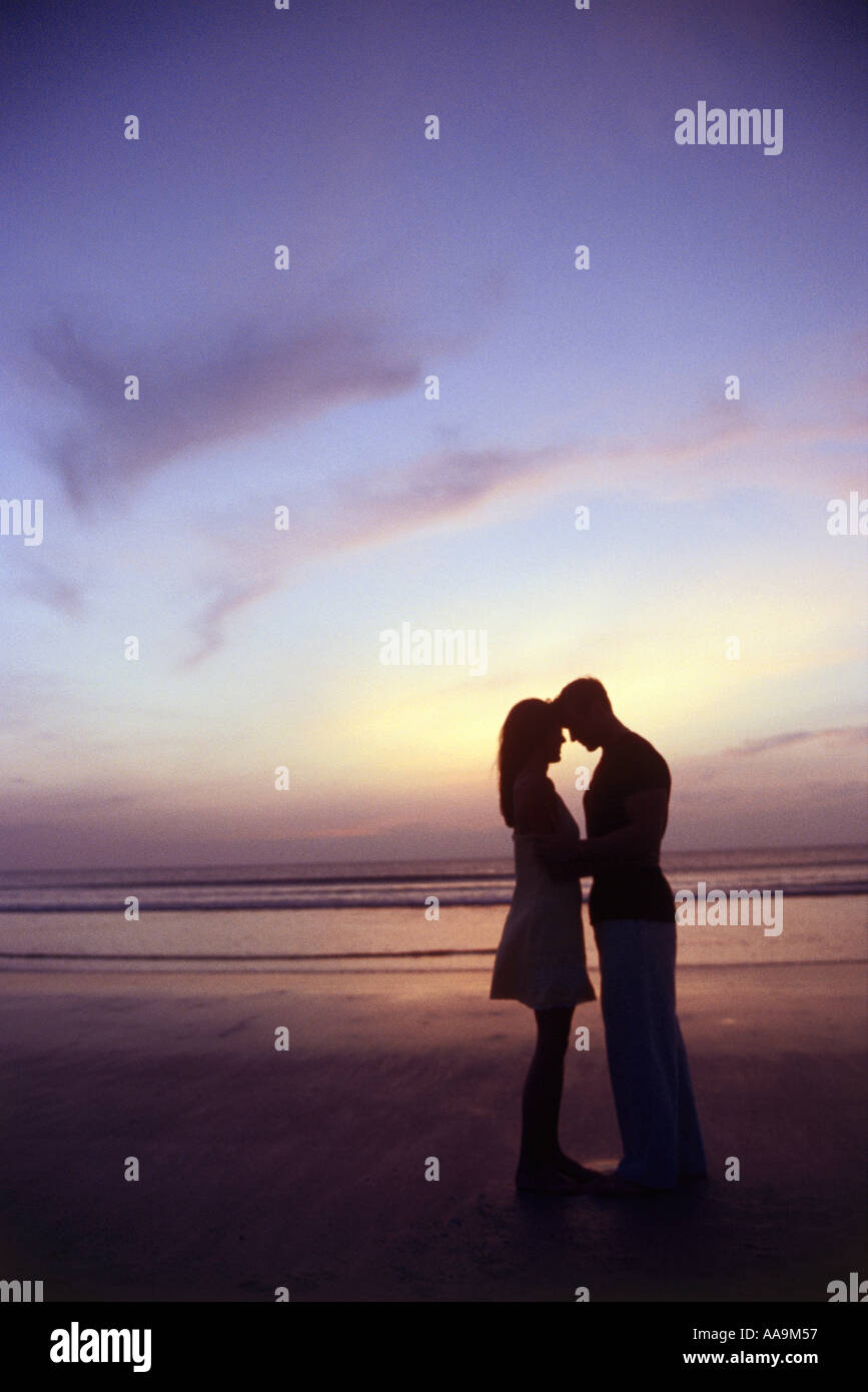 Silhouette d'un jeune couple ensemble à la plage Photo Stock