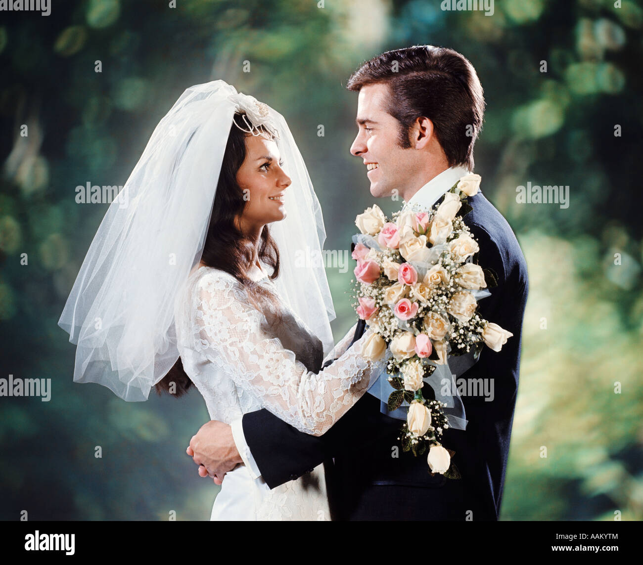 1970 EPOUSE GROOM HUGGING ADOPTER FACE À FACE HOMME FEMME COUPLE BOUQUET Photo Stock