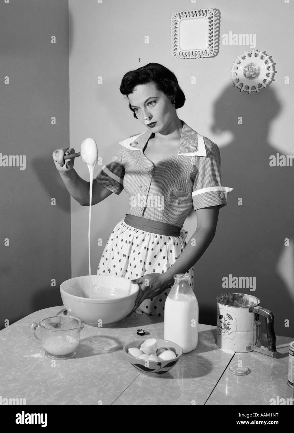 Femme au foyer des années 60 dans la pâte collante de mélange cuisine Photo Stock