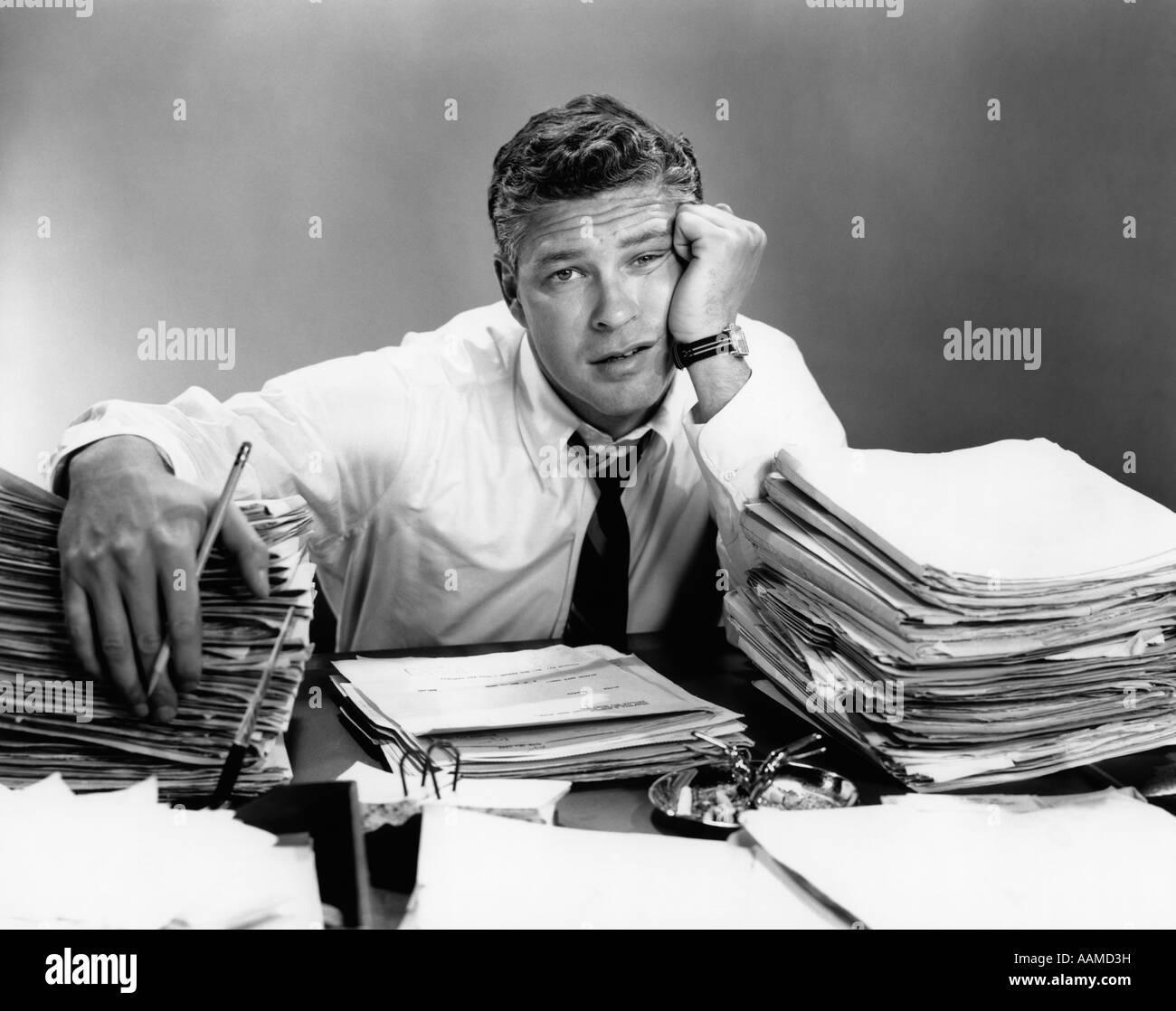 1950 PORTRAIT MAN surchargé de travail AVEC UN BUREAU PLEIN DE PAPIERS Photo Stock