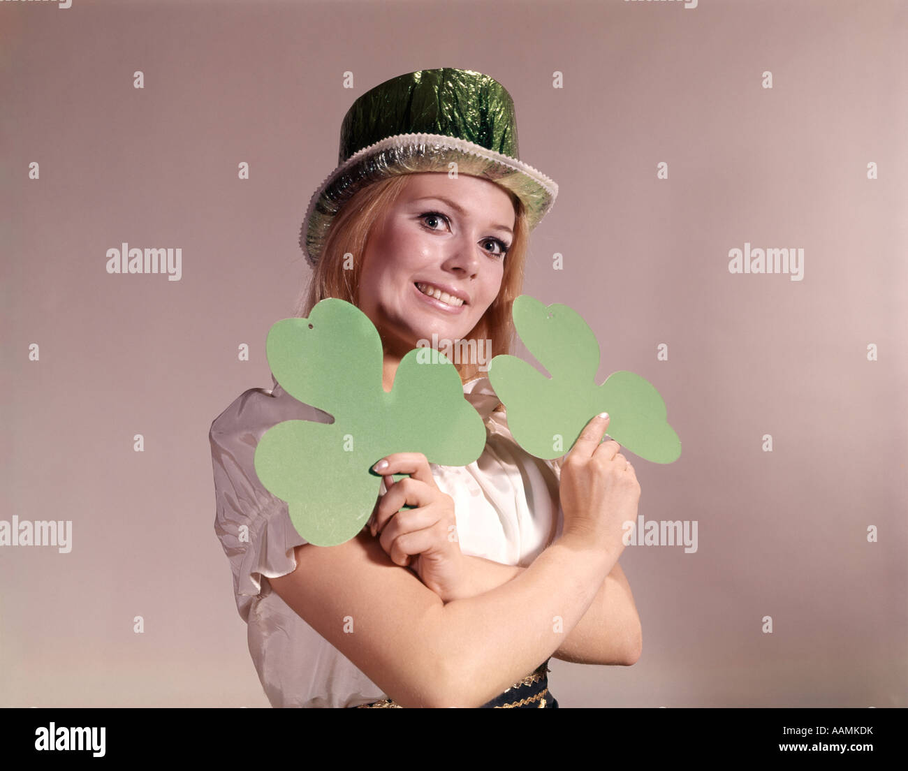 Années 1960 Années 1970 RETRO IRISH WOMAN SMILING HOLDING GREEN TRÈFLES ET WEARING GREEN PARTY HAT Photo Stock