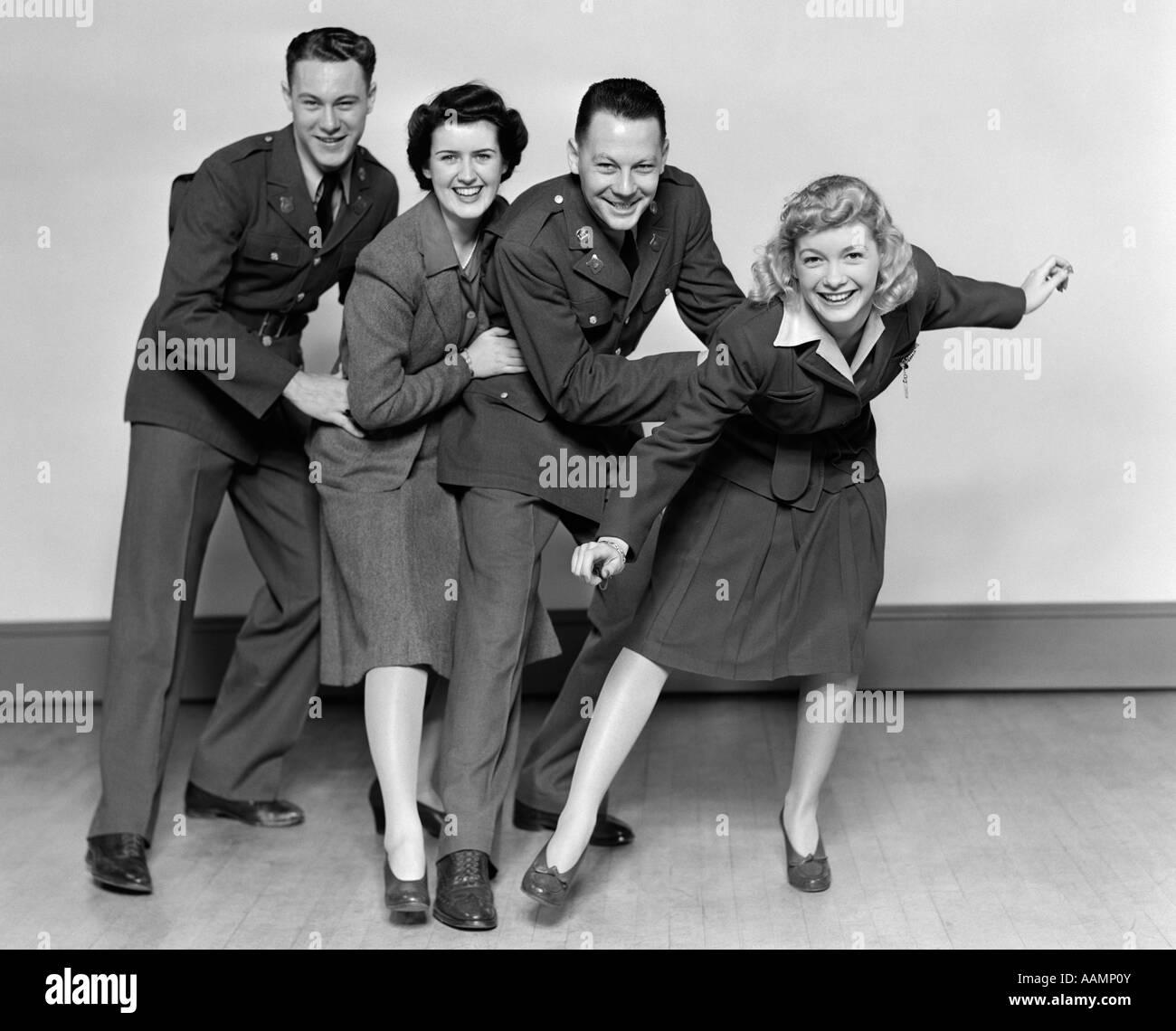 1940 LIGNE CONGA DEUX HOMMES ET DEUX FEMMES SOLDATS DANCING SMILING AT CAMERA Photo Stock