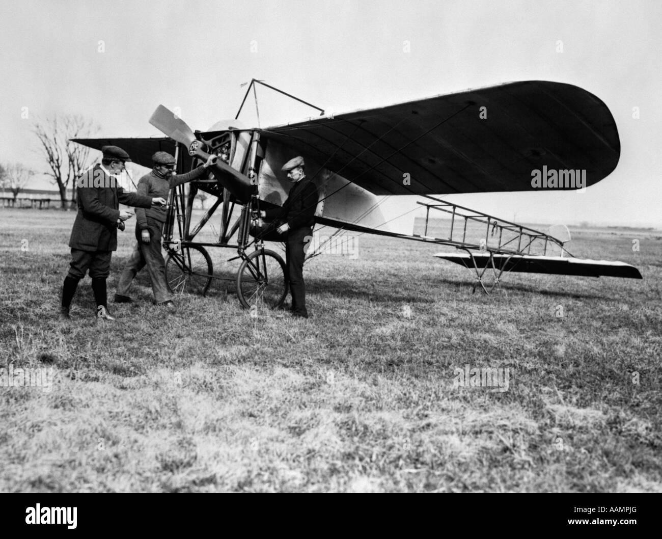 1910 GROUPE DE TROIS HOMMES DEBOUT DEVANT UN MONOPLAN PRÉCOCE AVEC MAIN SUR PROPELLER Banque D'Images