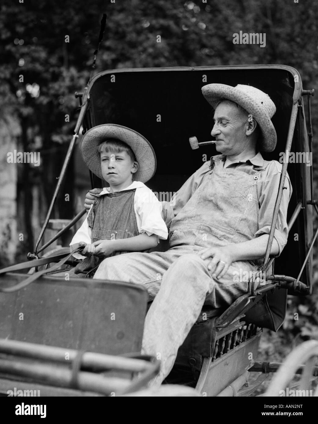 1930 Farm Boy & Grand-père dans des combinaisons et des chapeaux de paille assis dans de petits BUGGY Photo Stock