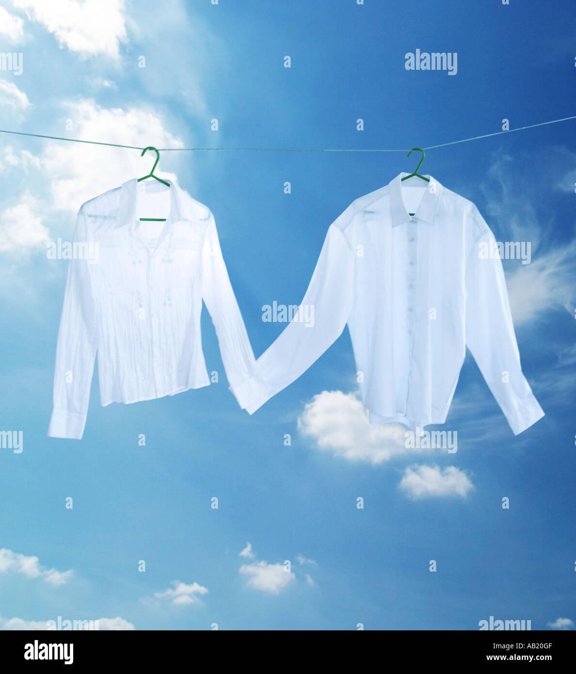 Chemise blanche sur une ligne de lavage holding hands Photo Stock