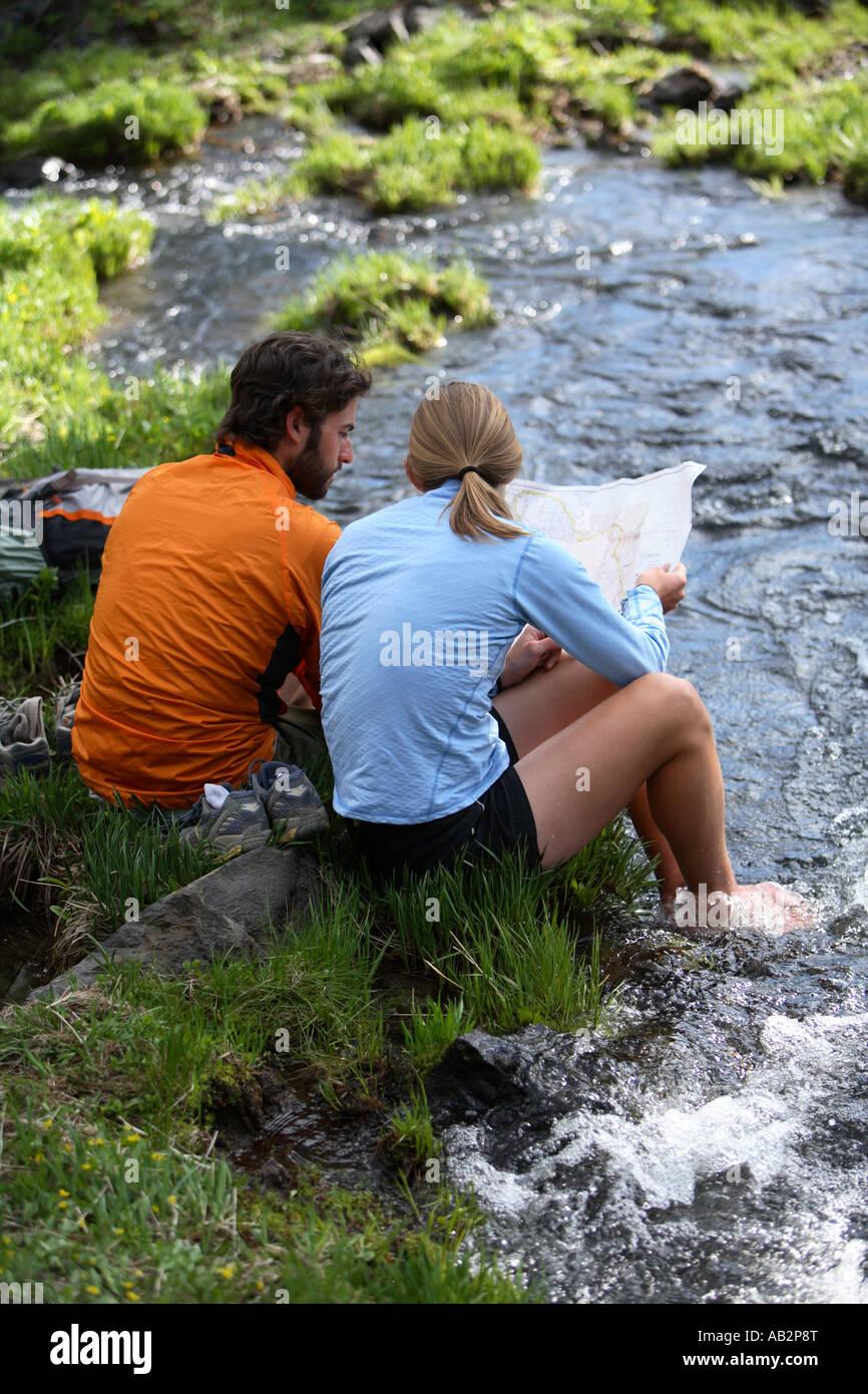 Couple de randonnée s'asseoir par un courant de voir la carte Photo Stock
