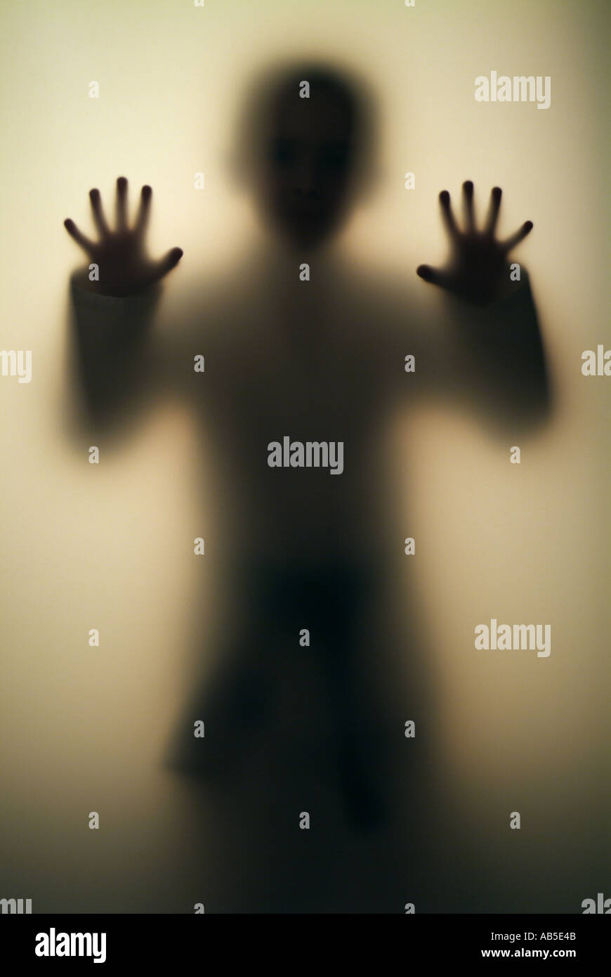 Boy 7, 8, 9, 10, 11, 12, 13, 14 ans figure derrière la paroi transparente Photo Stock