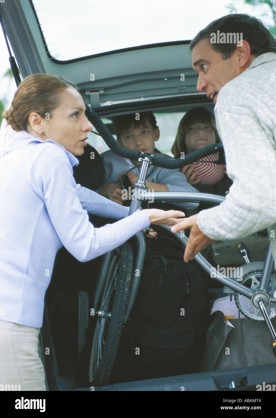 Mettre les parents en vélo coffre de voiture et à discuter pendant que les enfants regardent à partir de la location Banque D'Images