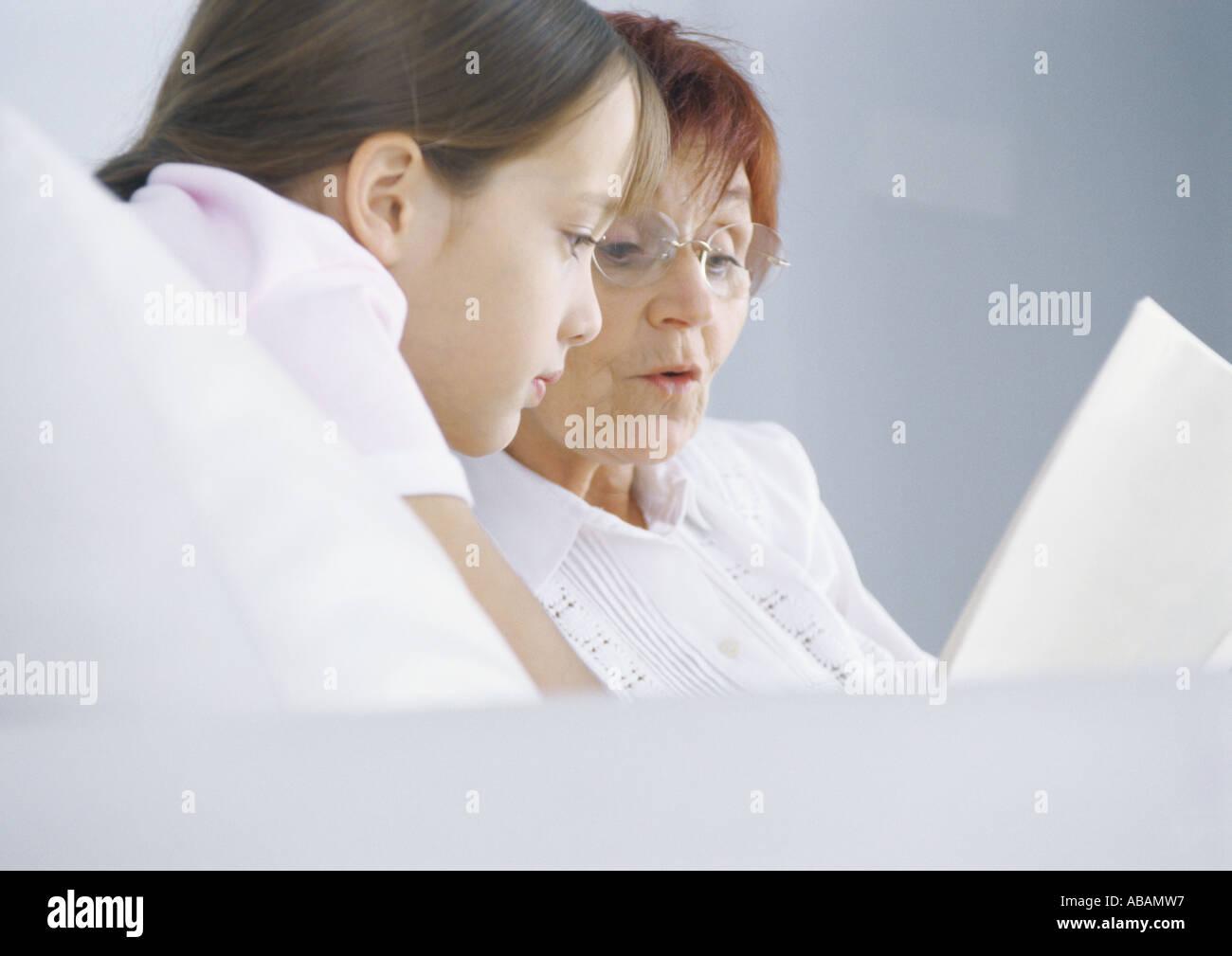 Girl reading book avec grand-mère Photo Stock