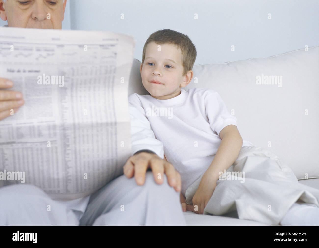 Garçon assis sur le canapé à côté de grand-père pendant qu'il lit journal Photo Stock