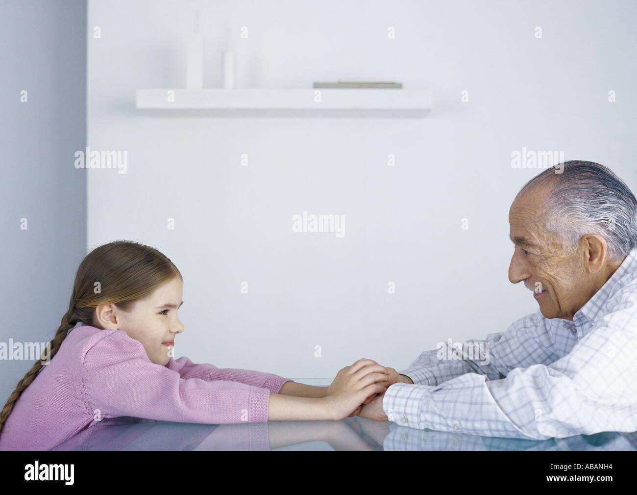Grand-père et fille assise en face de l'autre, à table, se tenant la main Photo Stock