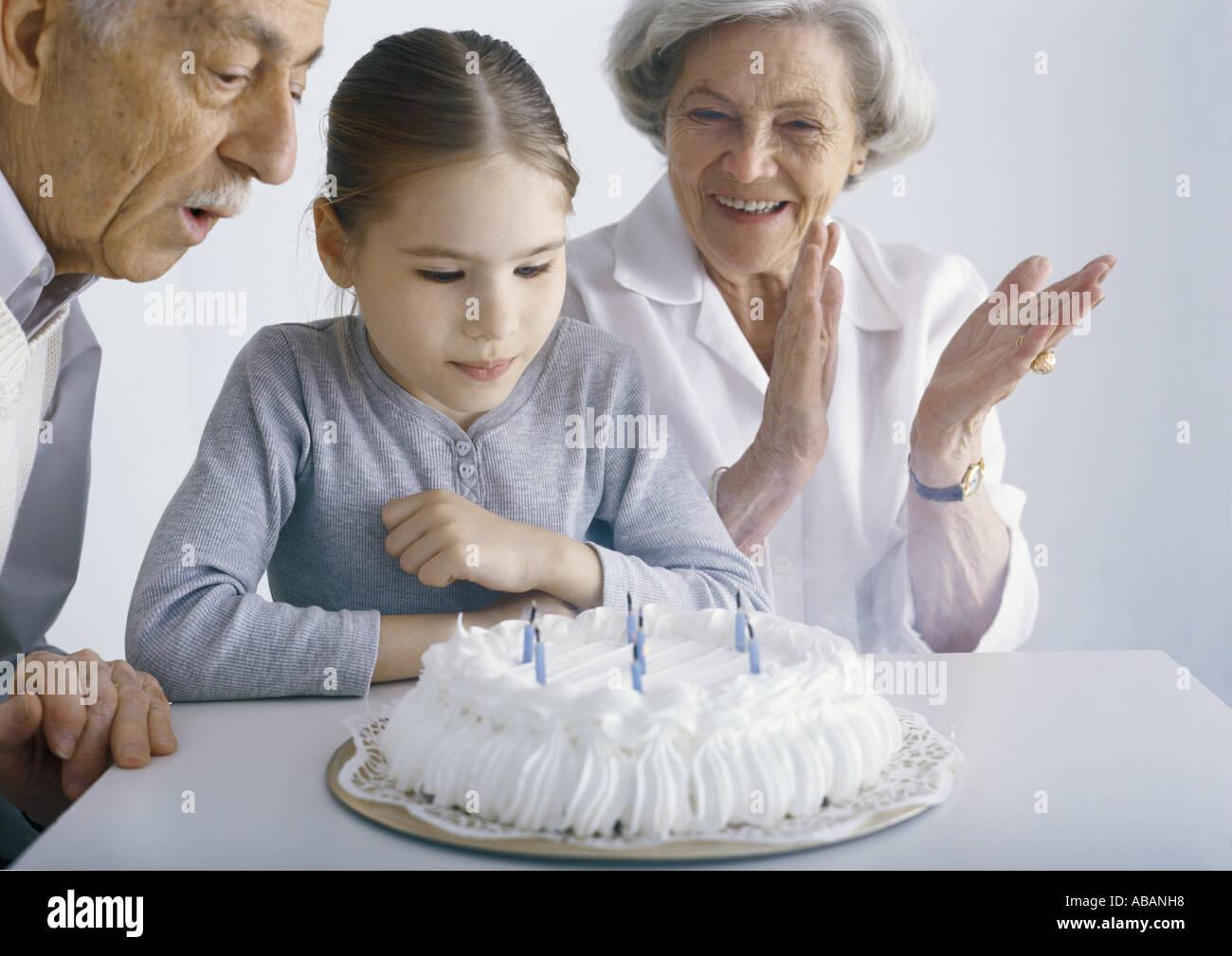 Fille aux grands-parents, réunis autour du gâteau d'anniversaire Photo Stock