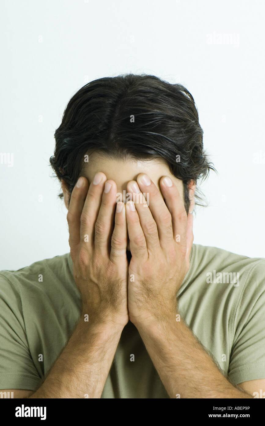 L'homme qui couvre le visage avec les mains, portrait Photo Stock