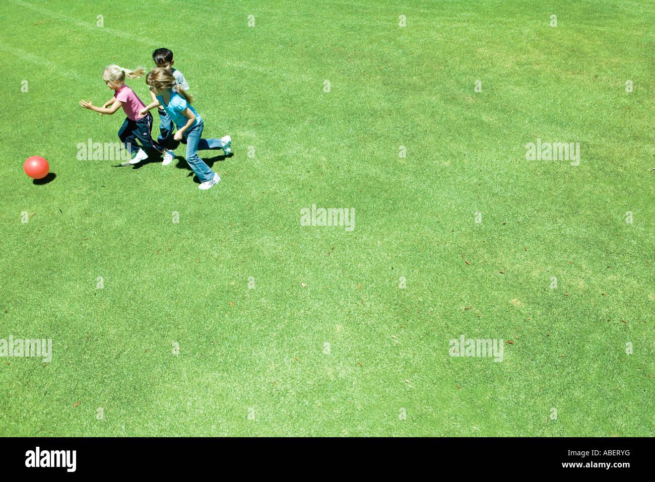 Les enfants jouer au ballon sur l'herbe Photo Stock