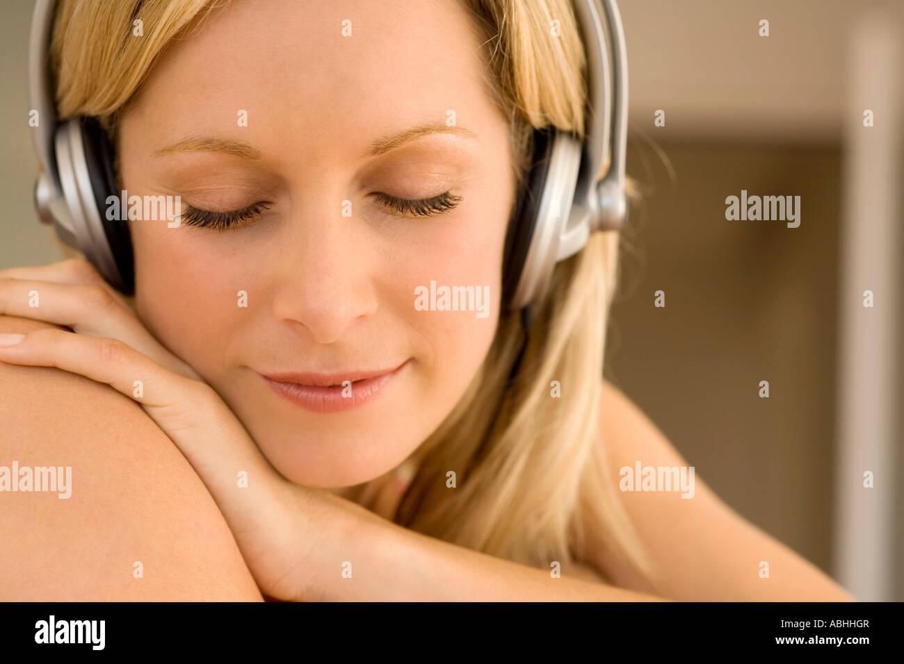Jeune femme d'écouter de la musique avec des écouteurs Photo Stock