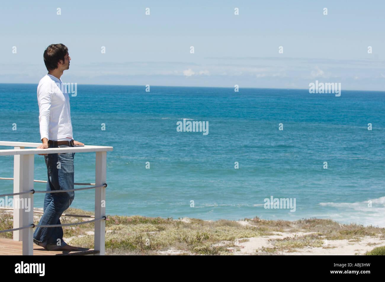Young man leaning against balustrade, regardant la mer Banque D'Images