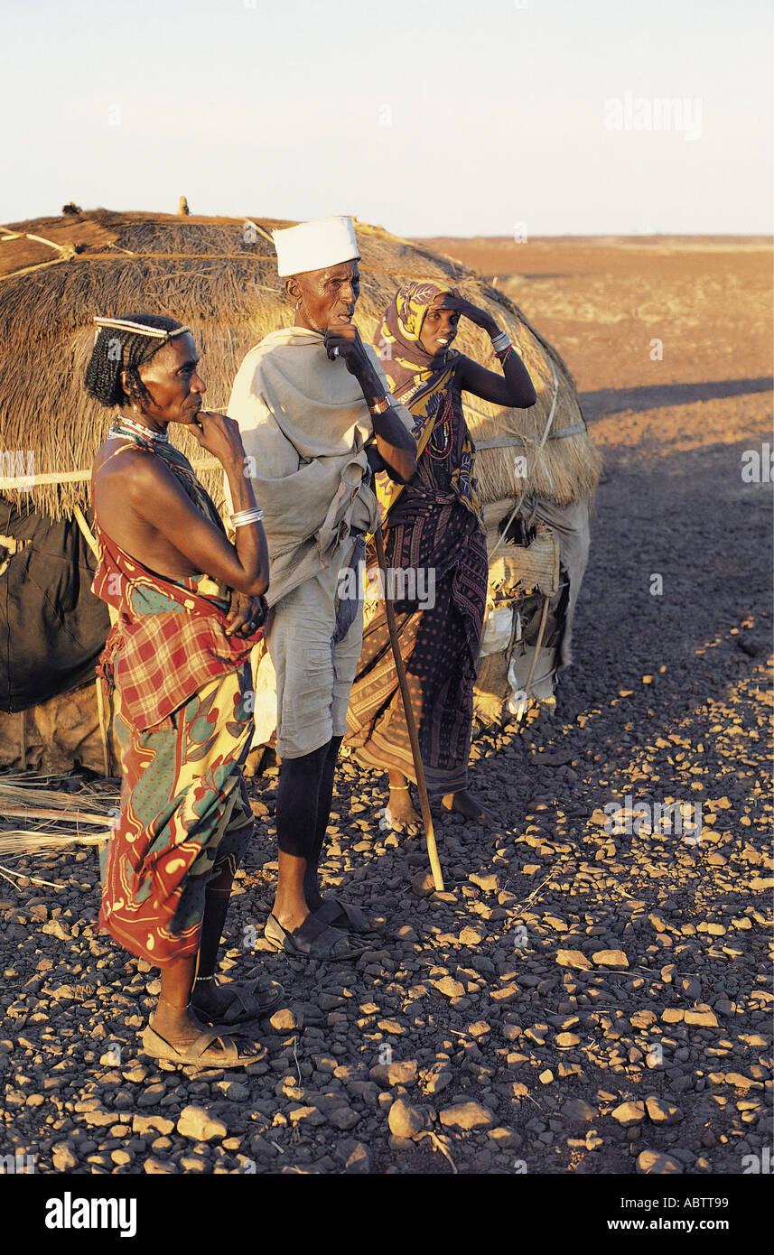 Vieux homme Gabbra avec son épouse et une jeune femme se tient en dehors de leur hutte dans le désert pierreux Photo Stock