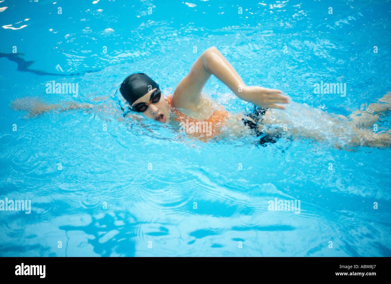 Woman swimming in pool avec cap et lunettes sur Photo Stock