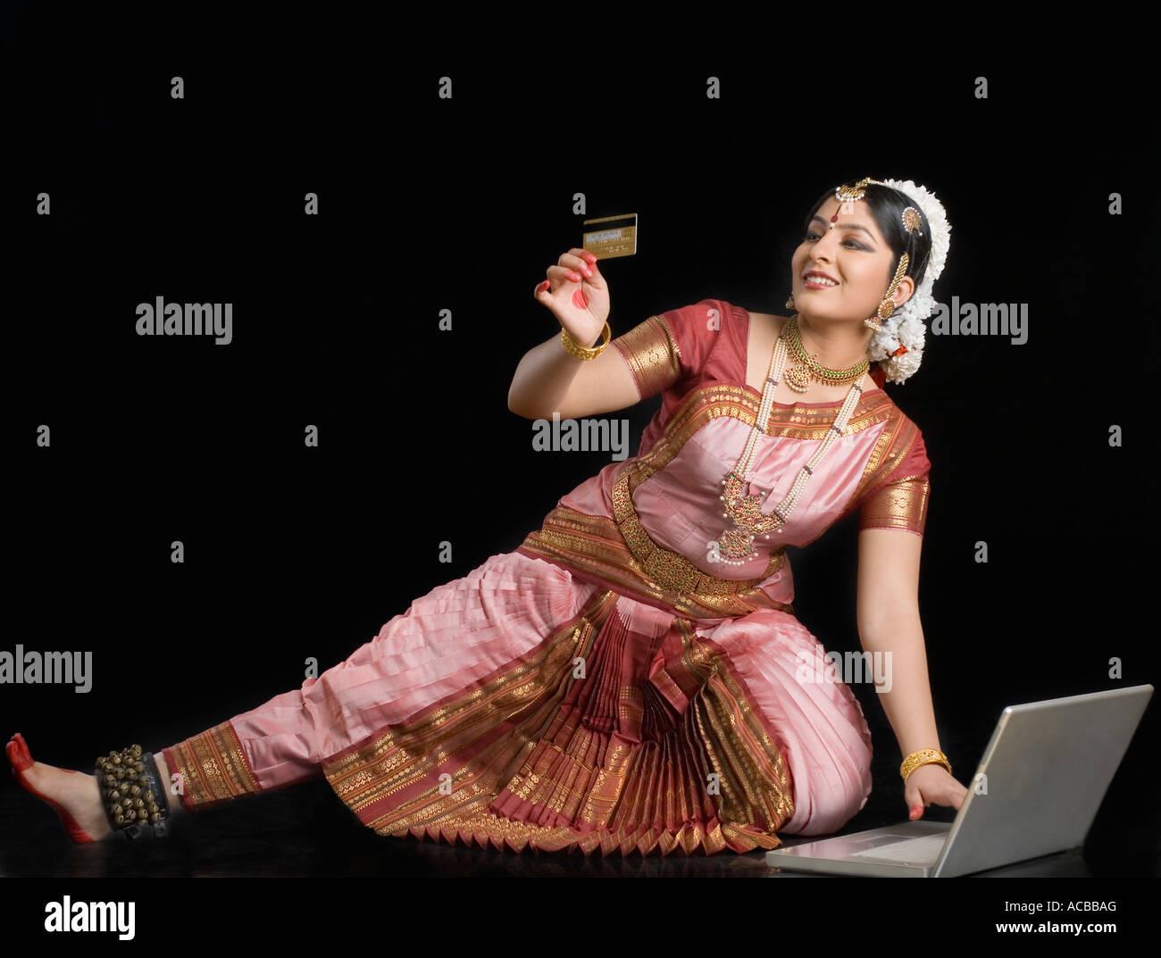 Jeune femme tenant une carte de crédit et l'aide d'un ordinateur portable Photo Stock