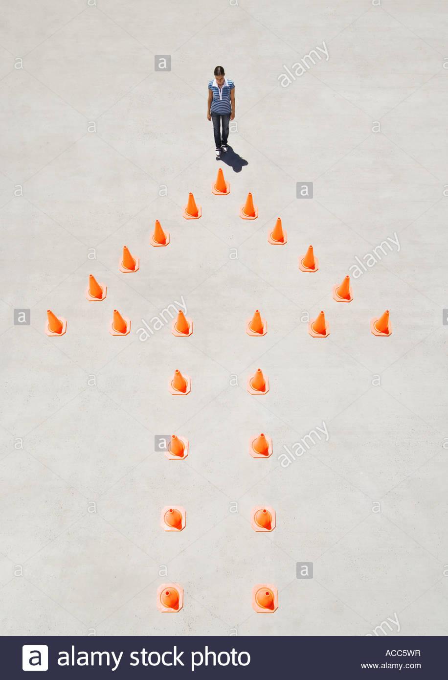 Cônes de circulation formant flèche avec une femme en haut Photo Stock