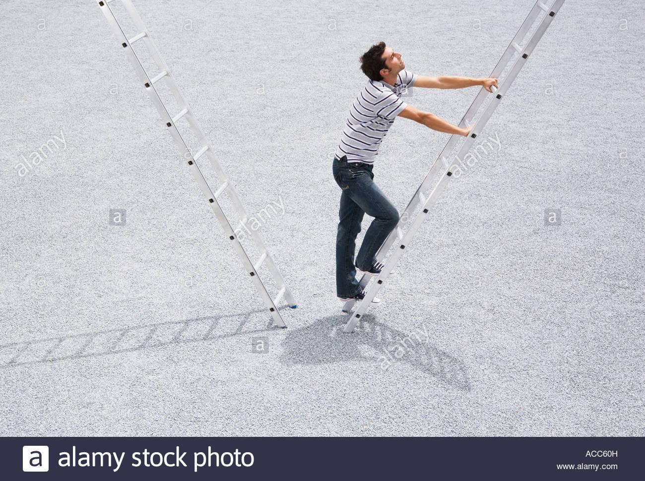 Escalade à l'extérieur de l'échelle de l'homme Photo Stock