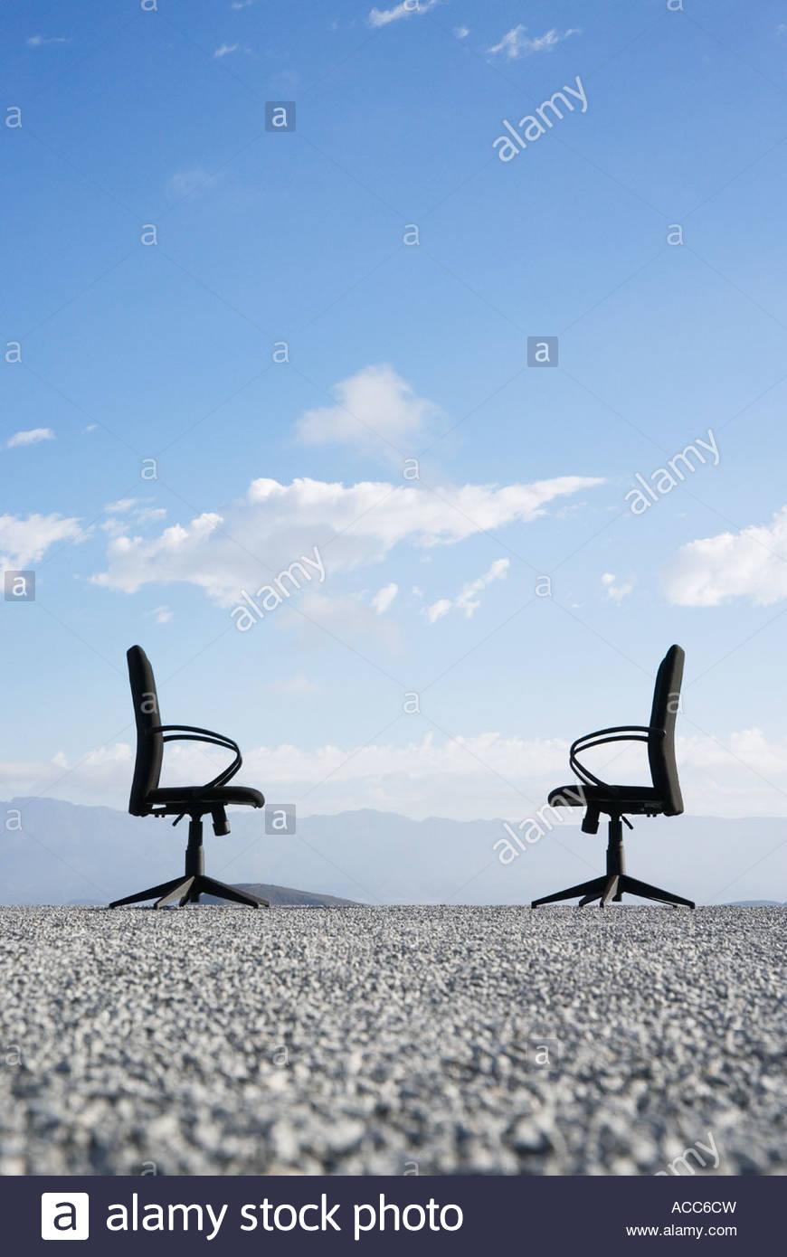 Deux chaises de bureau sur un terrain plein de cailloux Photo Stock