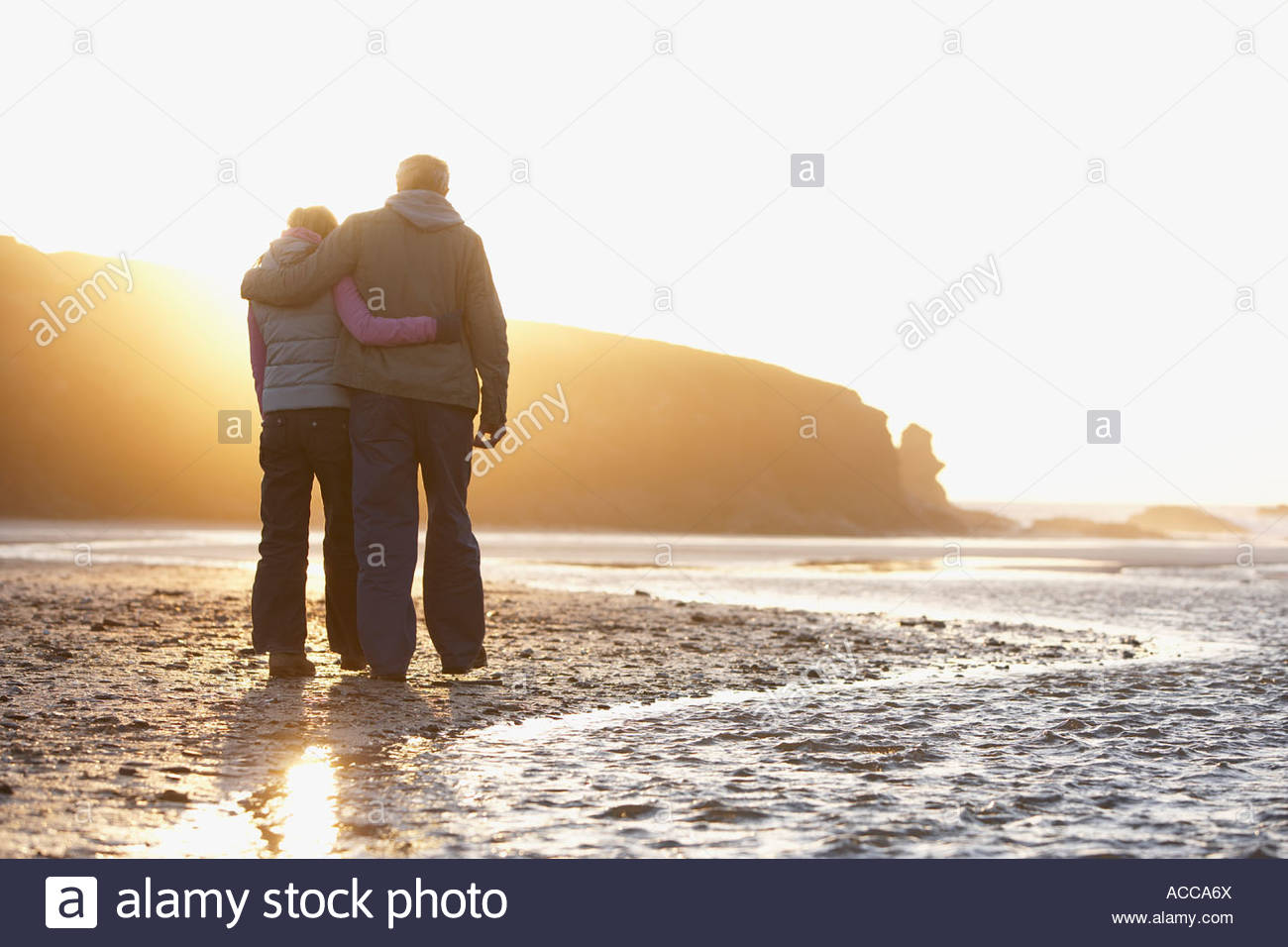 Heureusement couple embracing marchant sur la plage Photo Stock