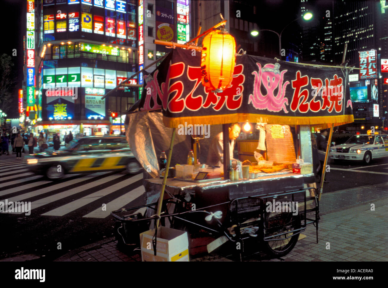 Vente Panier Octopus balles takoyaki sur coin de rue dans le centre-ville de Tokyo la nuit Photo Stock