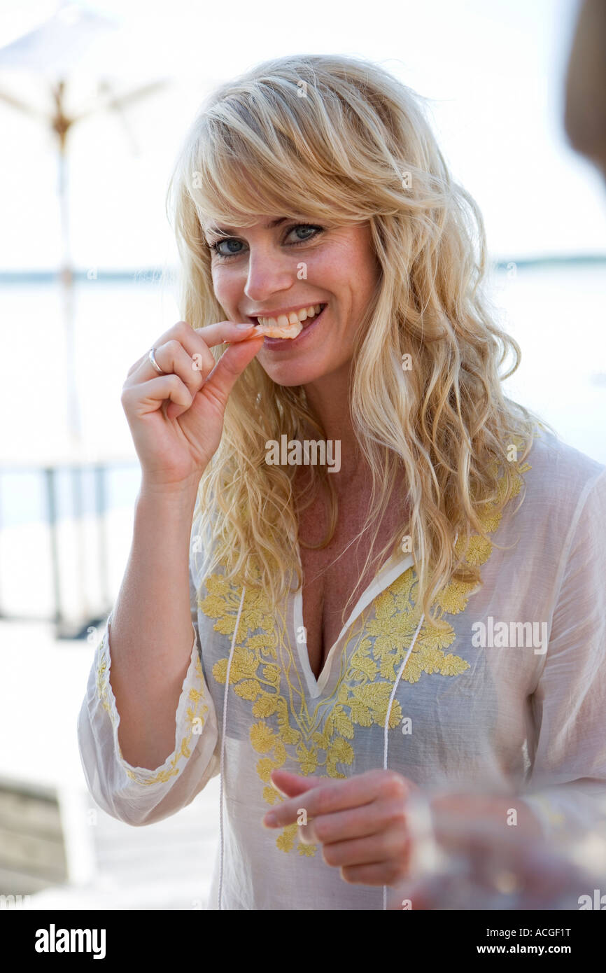 Une blonde woman munching sur un en-cas. Photo Stock