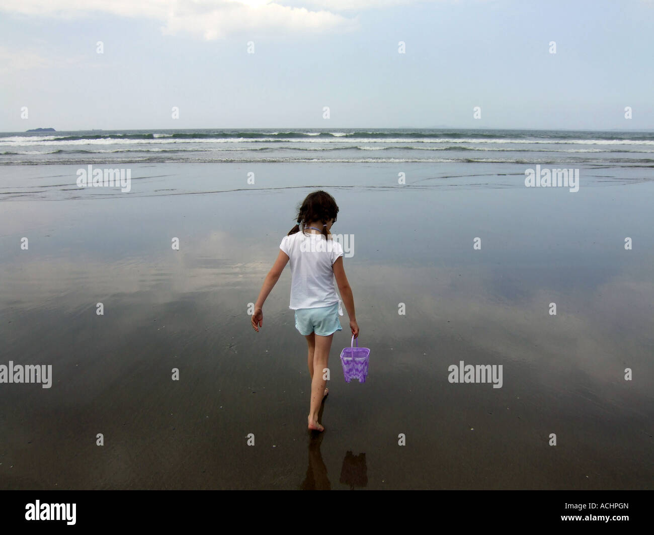 Fille qui marche sur la mer portant un seau, UK Photo Stock