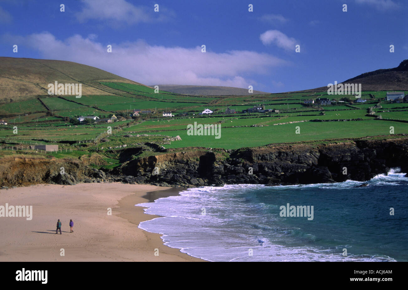 Les gens qui marchent sur la plage de Clogher, sous le patchwork des champs verts. Péninsule de Dingle, comté Photo Stock