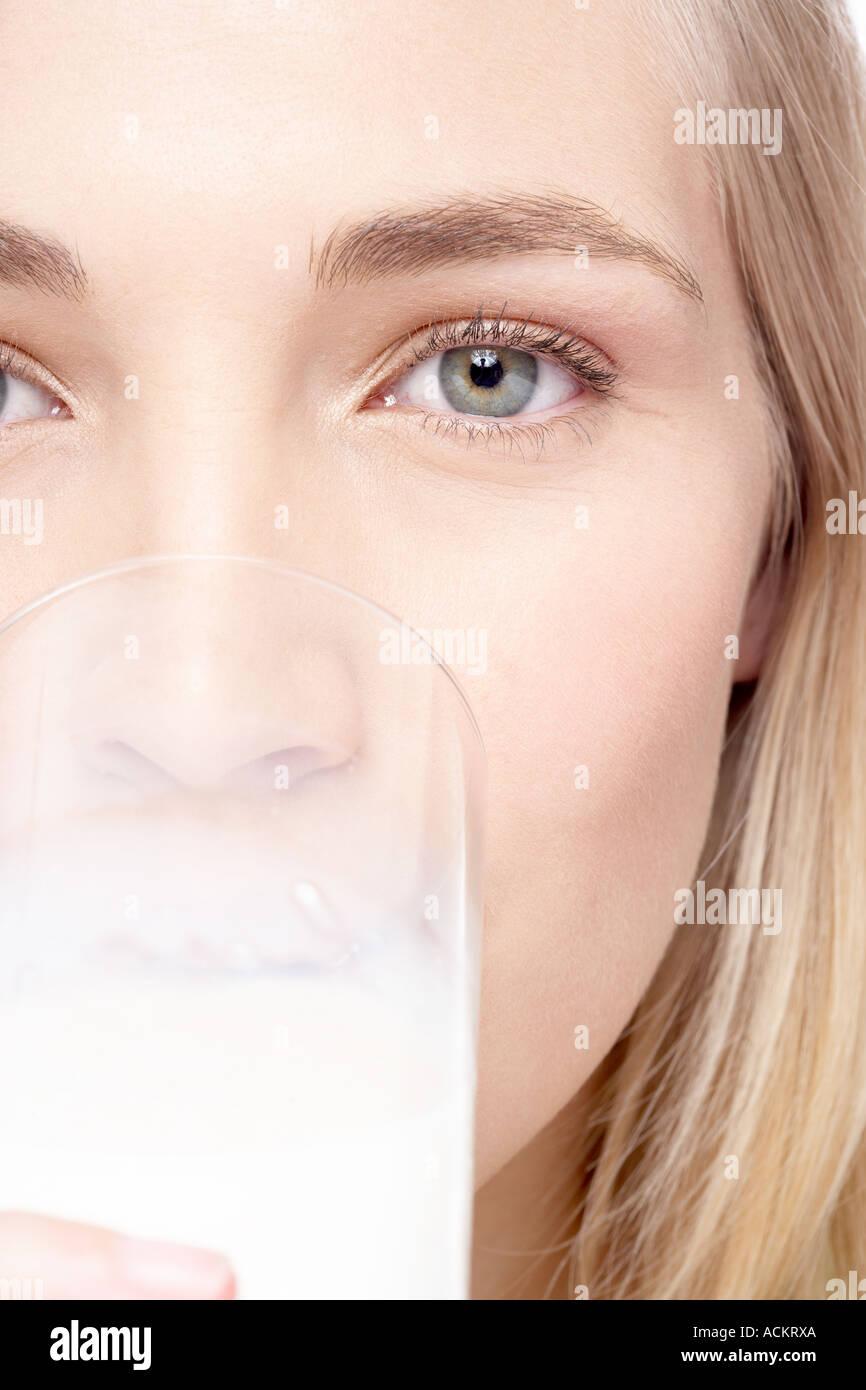 Une jeune femme regardant la caméra de boire Photo Stock