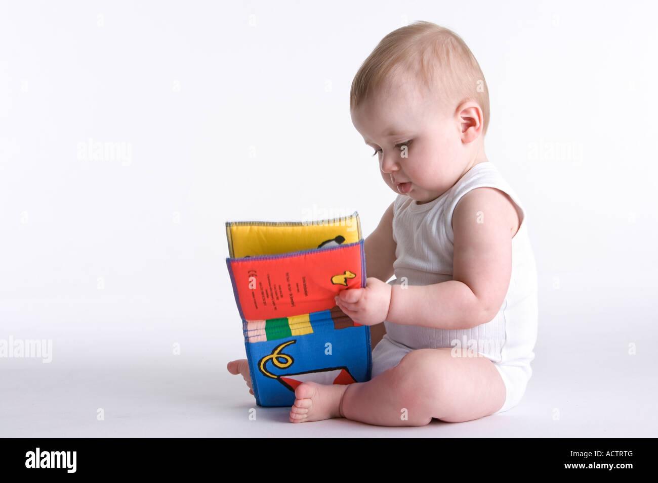 Bébé garçon avec un livre de jouets textiles Photo Stock