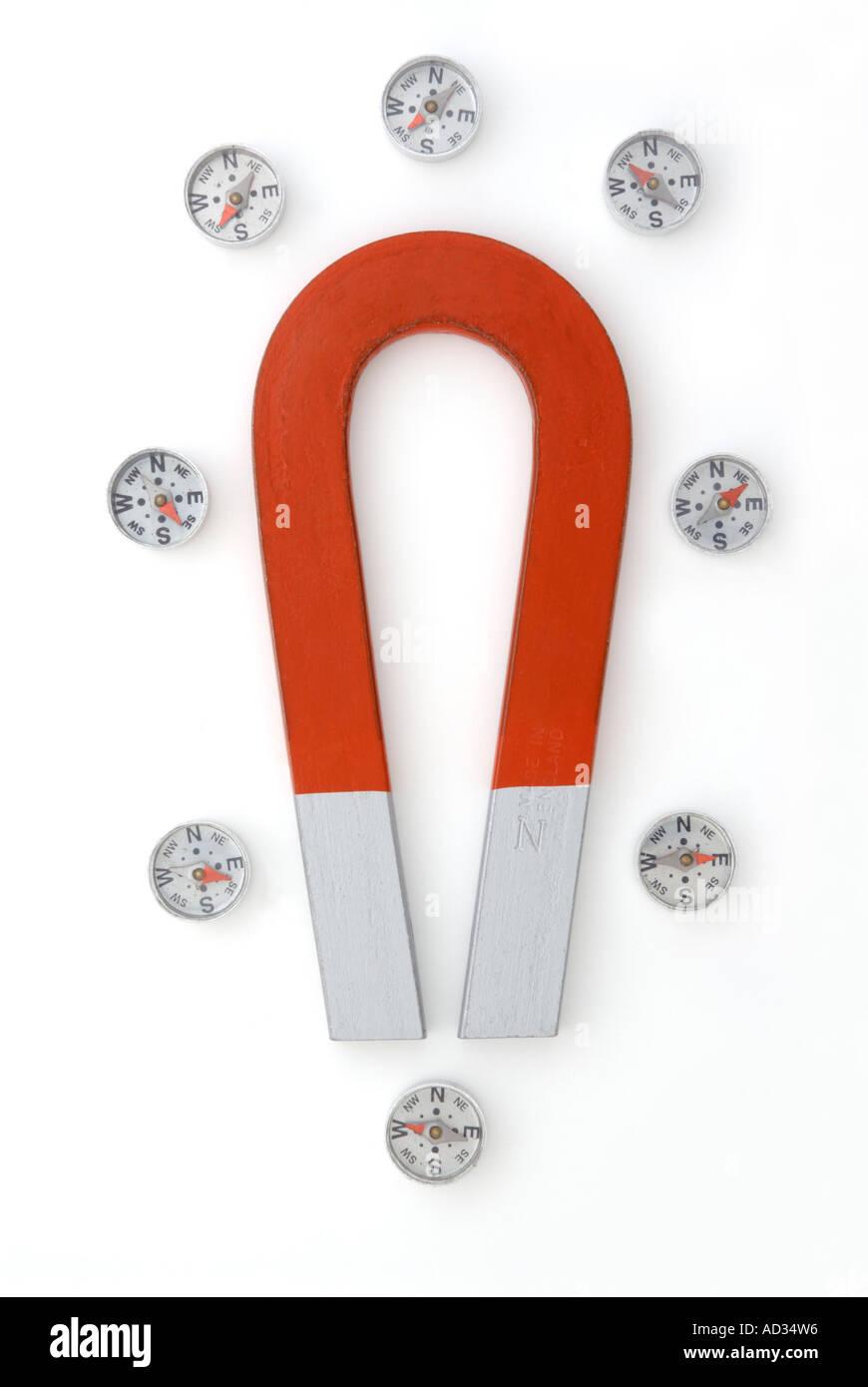 Aimant à deux pôles en forme de fer à cheval avec plusieurs boussoles montrant effet de champ magnétique Photo Stock
