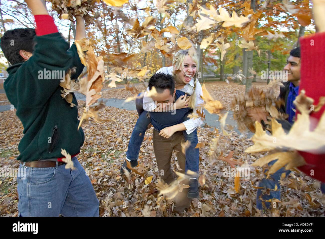 Cinq jeunes adultes hommes et femmes à l'automne laisse jeter vie Photo Stock