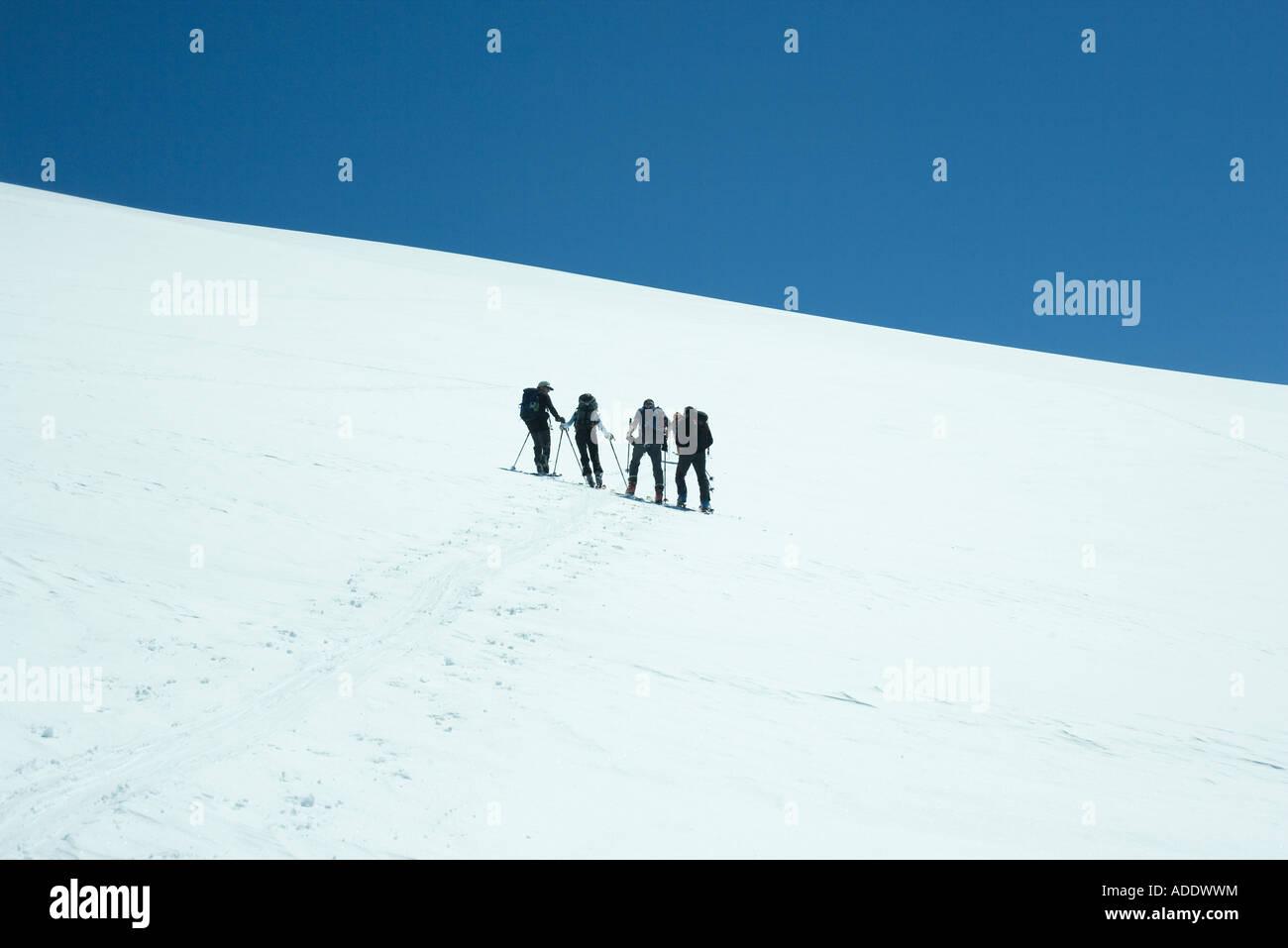 Les skieurs debout côte à côte sur la pente, vue arrière Photo Stock