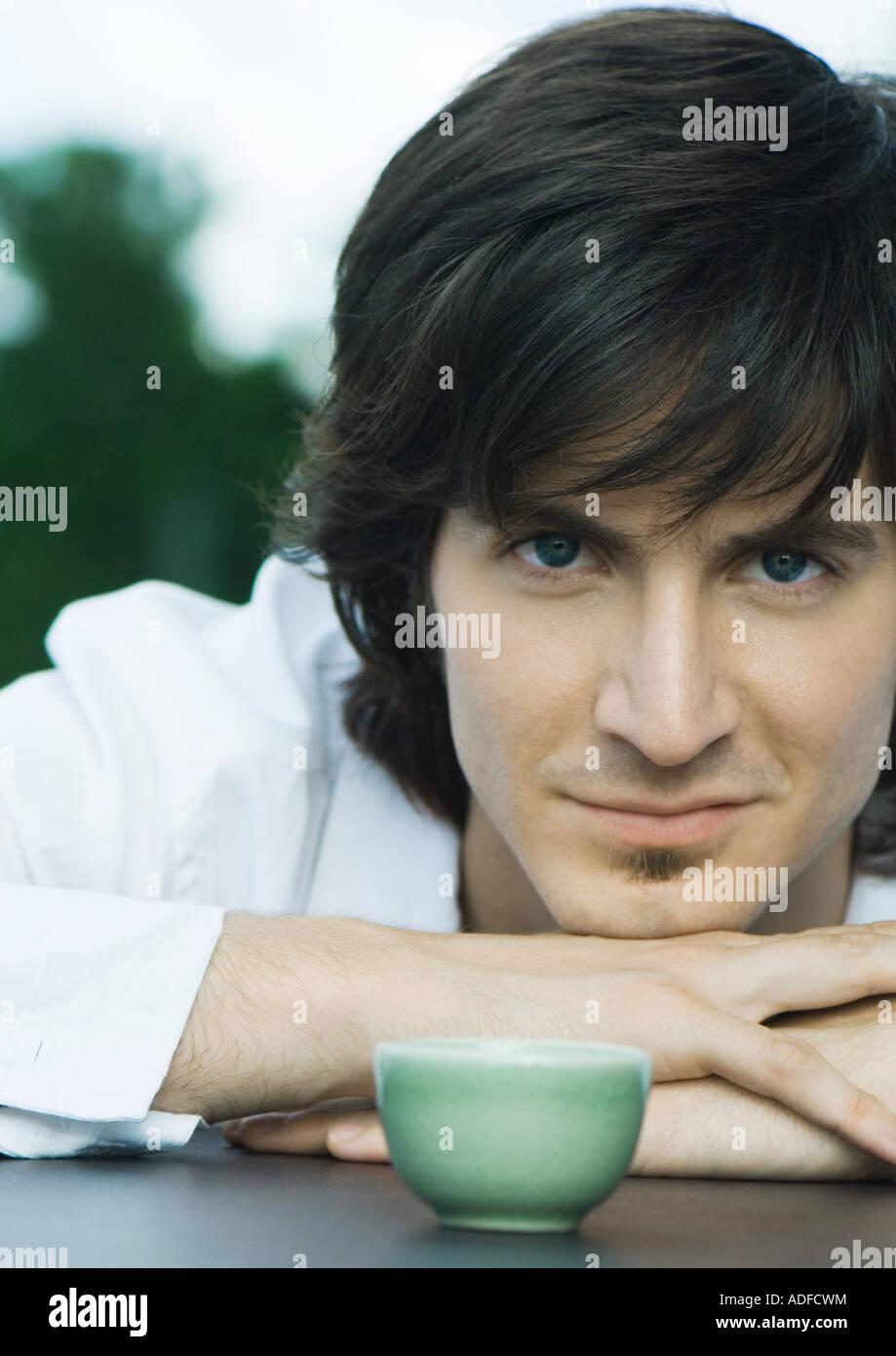 Man resting head on arms à côté de tasse de thé, looking at camera Banque D'Images