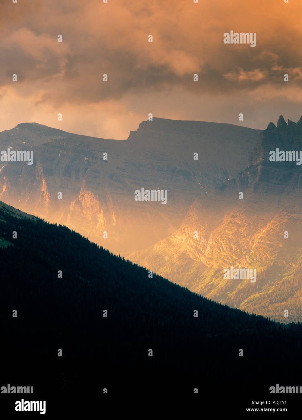 Soleil nuages peeking through et brillant sur les montagnes du Parc National des Glaciers du Montana Photo Stock