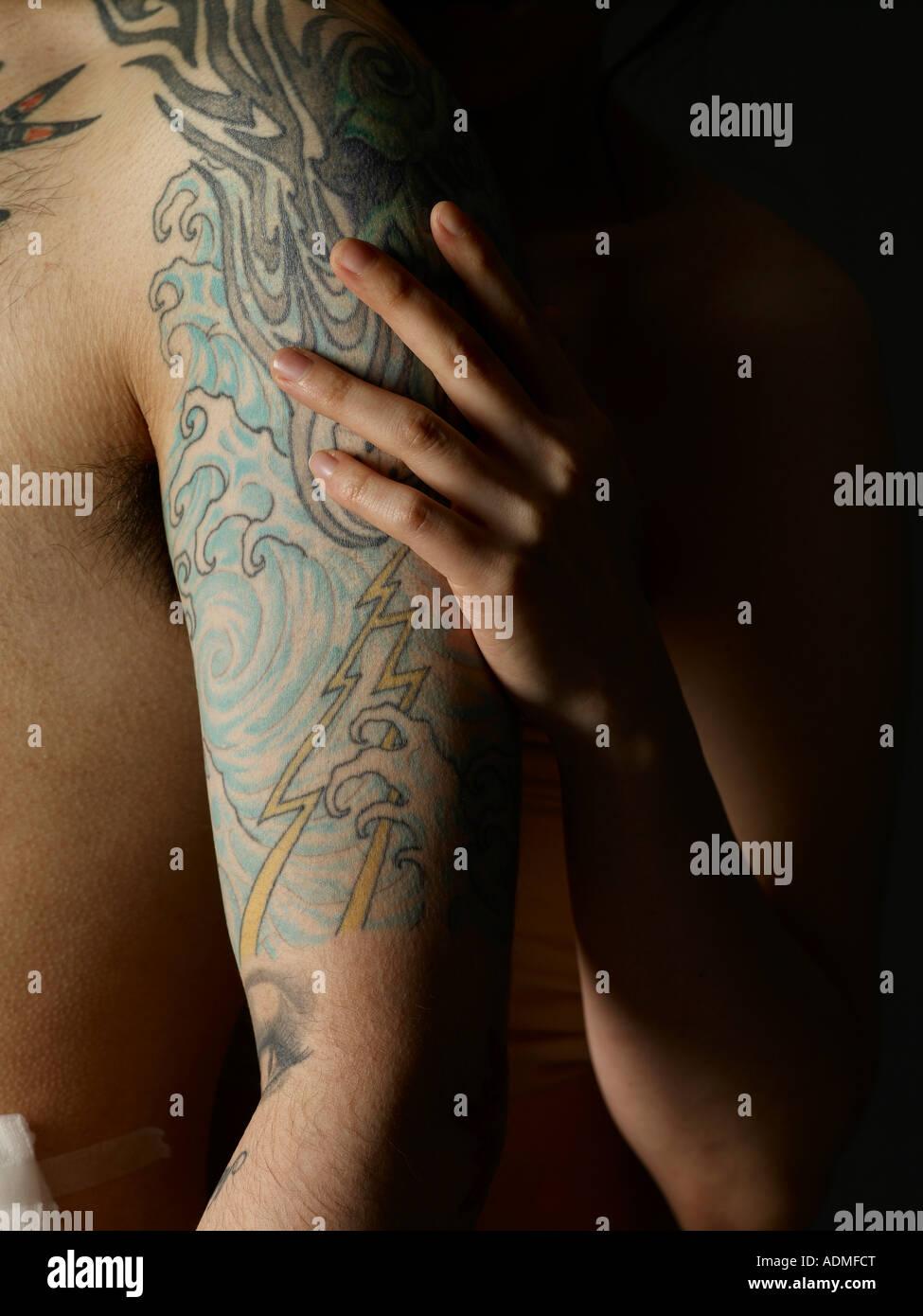 La Main De Femme Sur Les Bras De L Homme Aux Tatouages Banque D