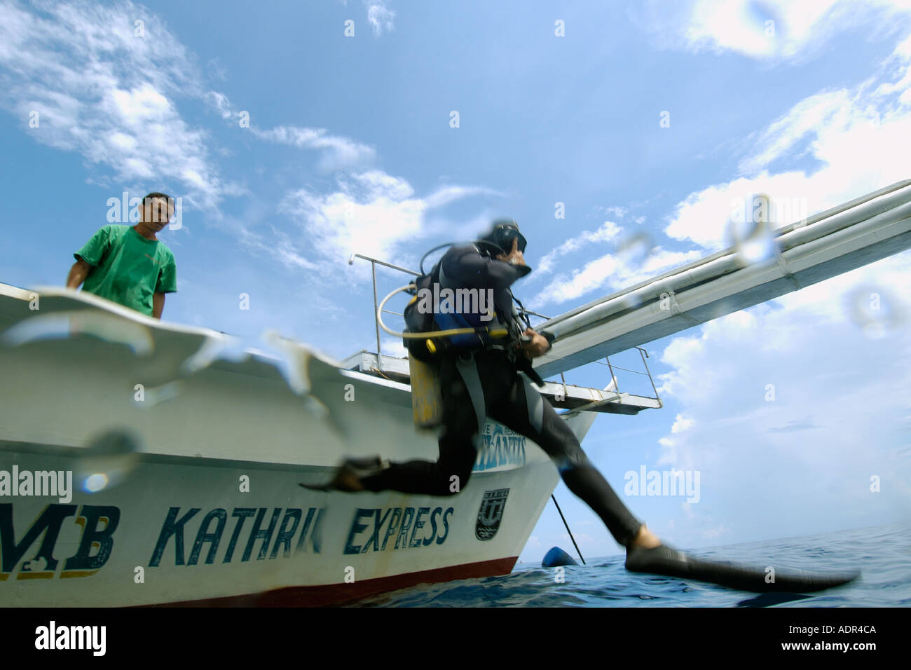 Plongeur effectue un grand pas pour entrer dans l'eau avant la plongée Apo Island Marine Reserve aux Philippines Photo Stock