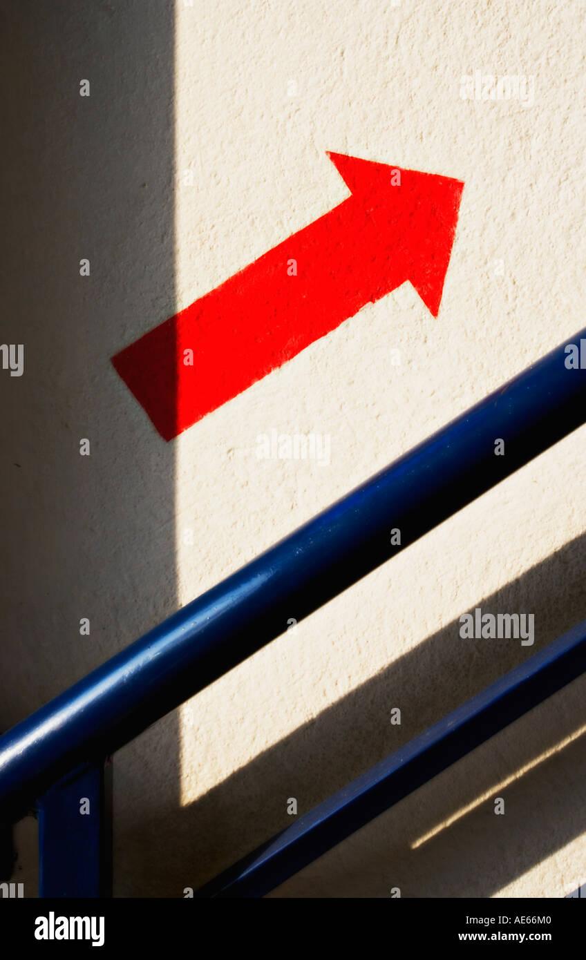Flèche rouge one way sign peints sur le mur à côté d'escalier Photo Stock