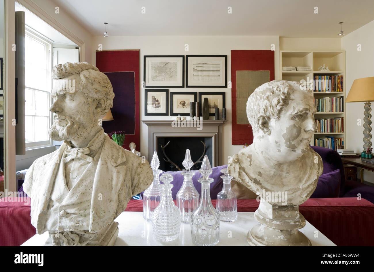 Des bustes de plâtre et des carafes en verre sur un en haut dans une salle de séjour Photo Stock