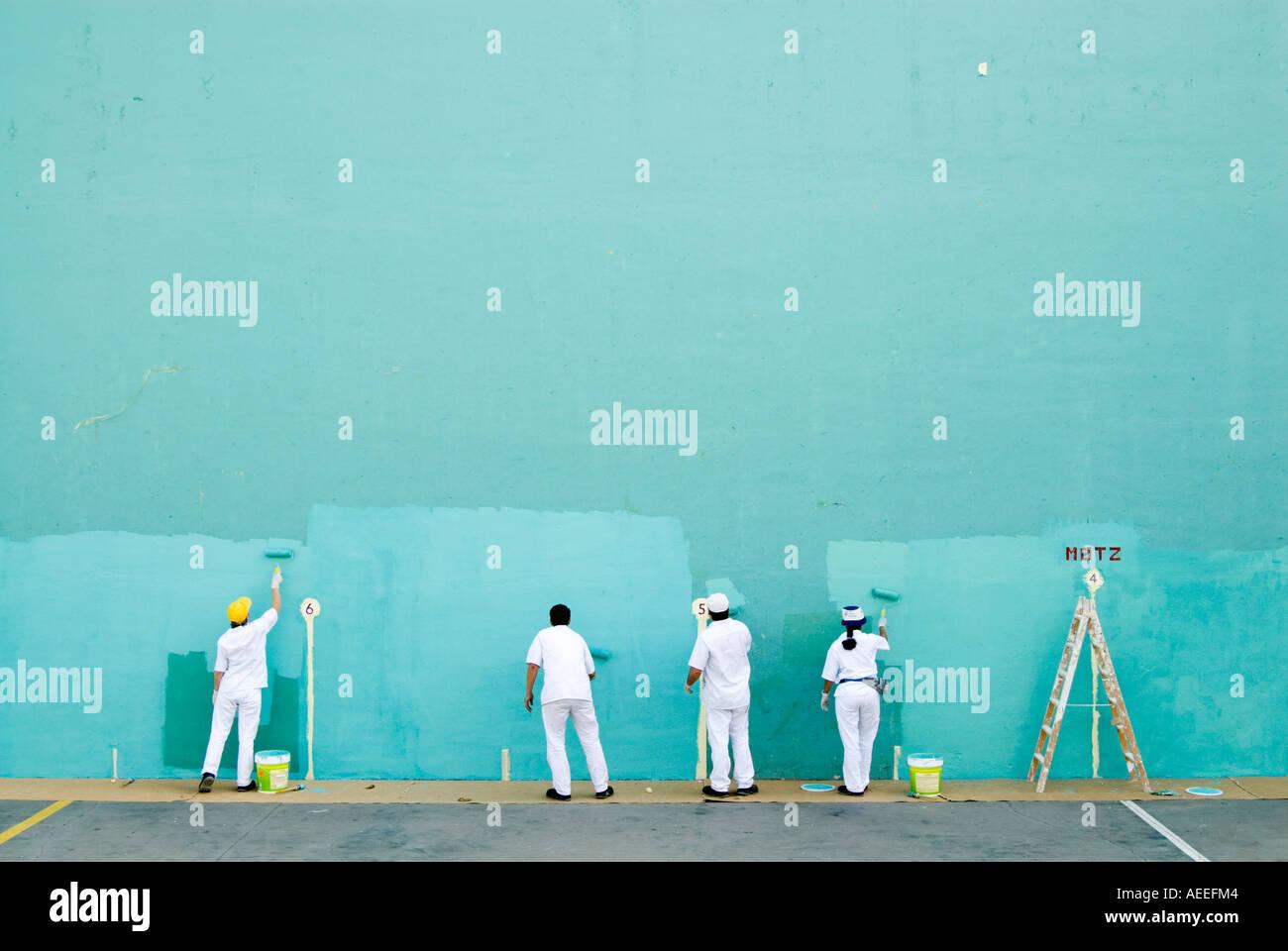 Équipe de travailleurs peinture grand mur blanc turquoise sur jeu de pelote basque, Espagne Photo Stock