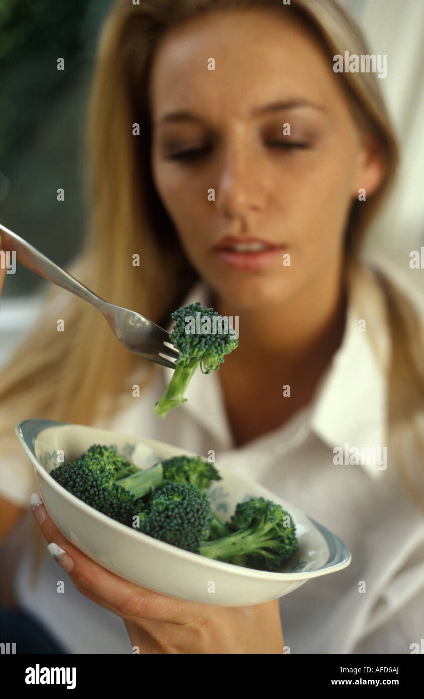 Woman eating broccoli Photo Stock